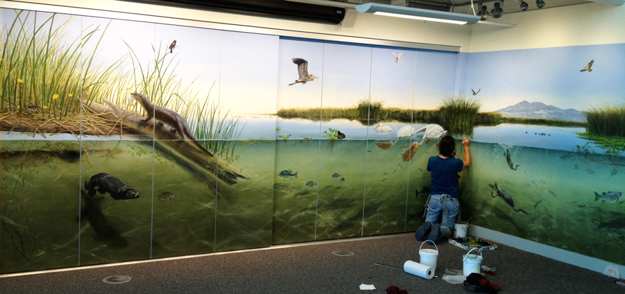 Ali Pearson installing the mural