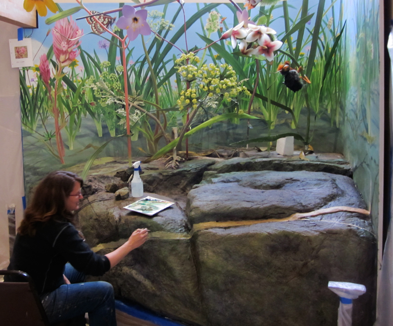 The serpentine flower mural being integrated into the diorama by another artist